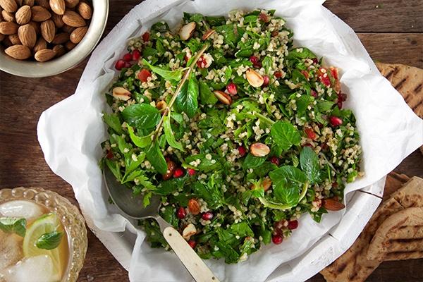 Ein orientalischer Salat mit frischen Kräutern und Bulgur sowie Tomatenstückchen in einer weißen Schale.