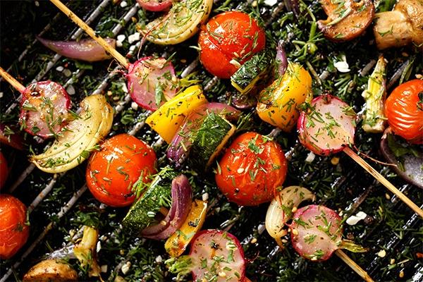 Gemüsespieße mit Tomate, Zwiebel und Paprika liegen auf dem Grillrost.