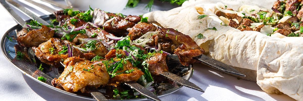 Grillfleisch ist auf einem Metallspieß aufgereiht und liegt auf einem silbernen Teller, daneben Wrapteig und weitere Spieße.