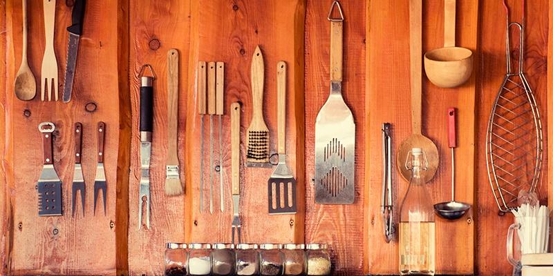 An einer Holzwand hängt unterschiedliches Grillzubehör, wie mehrere Fleischgabeln, ein Soßenpinsel, eine Grillbürste, Küchenhelfer, Grillzangen, ein Schöpflöffel und ein Fischbräter. Davor steht eine Glasflasche und ein Glas mit Plastikbesteck.