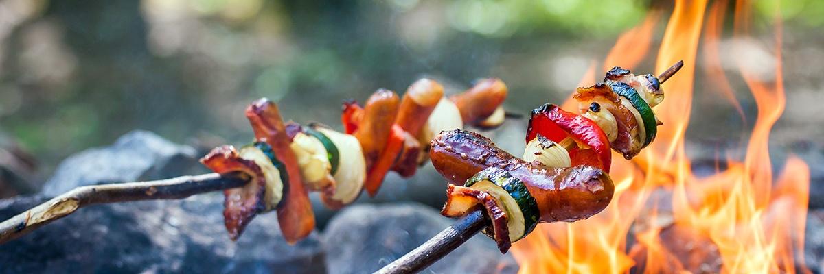 Grillspieße mit Würstchen, Paprika, Zucchini und Zwiebel auf einen Ast gereiht werden über einem Lagerfeuer gegrillt.