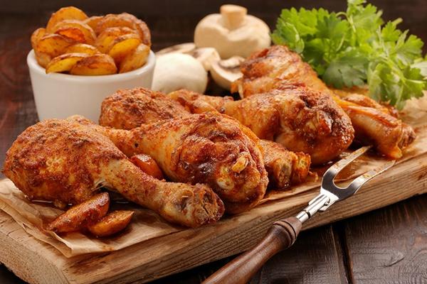 Fünf Hühnerkeulen liegen auf einem Holzbrettchen. Dahinter liegen Kräuter, Pilze und Kartoffelscheiben.