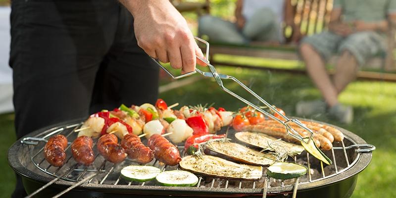 Auf einem runden Holzkohlegrill werden Gemüsespieße, unterschiedliche Bratwürste, Scheiben von Zucchini und Melanzani gegrillt. Mit einer Grillzange wird eine Zucchinischeibe gewendet.