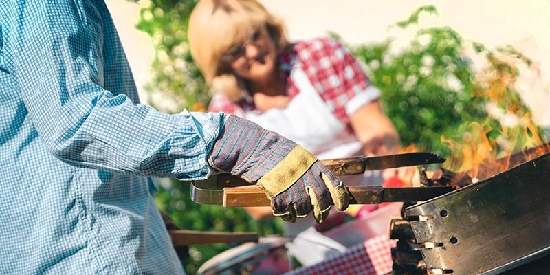 Ein Mann steht vor seinem Grill. Er trägt Schutzhandschuhe und hält eine Holzzange zum Wenden des Grillguts in seiner Hand.