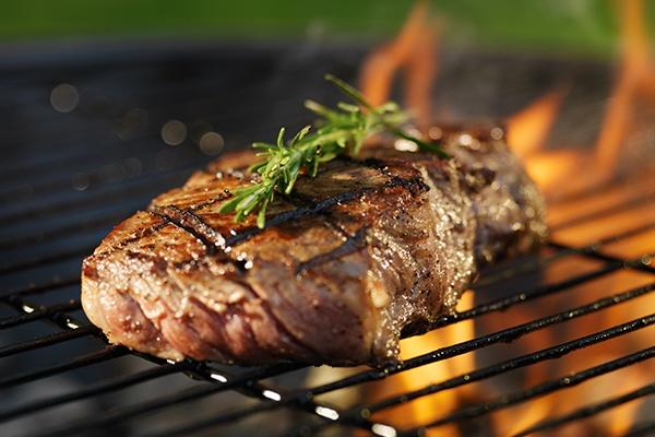 Ein mit Rosmarin garniertes Steak liegt auf einem Holzkohlegrill.