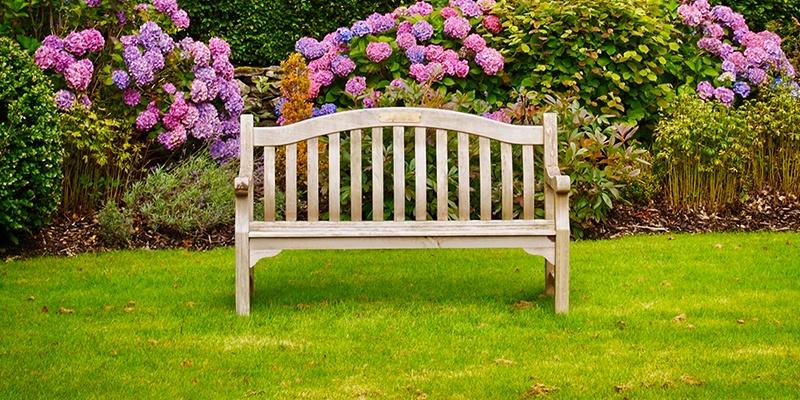 Eine Gartenbank, die auf der Wiese im Garten steht.