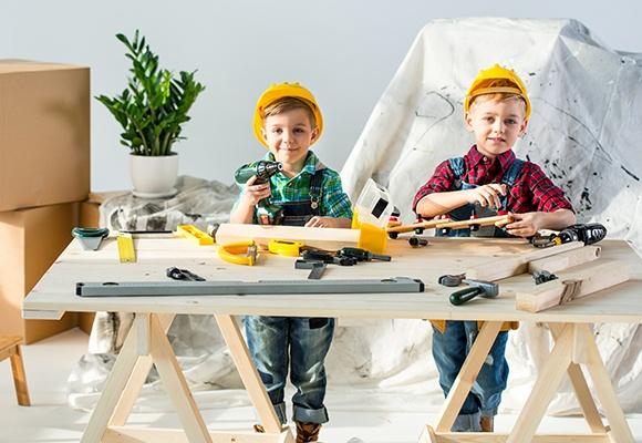 Zwei Jungen tragen jeweils einen gelben Schutzhelm, karierte Hemden und Latzhose. Der linke Junge hält in seiner rechten Hand einen Akkuschrauber. Der rechte Junge hält ein Werkstück in seinen Händen.