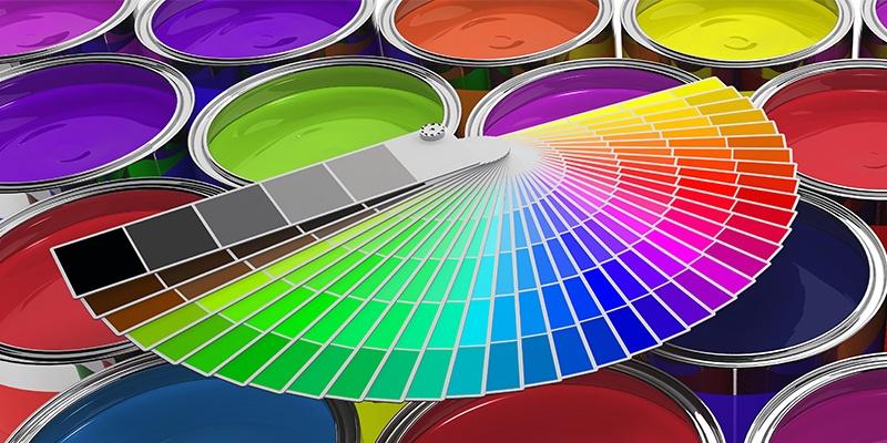 Viele unterschiedliche offene Farbdosen mit bunten Farben. Darauf liegt eine zu einem Fächer ausgebreitete Farbpalette.