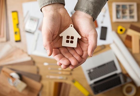 Zwei Hände halten ein kleines Holzhaus in den Händen. Im Hintergrund sieht man verschwommen einen Tisch auf dem verschiedene Dinge, wie eine Wasserwaage, ein Rechner, ein Stift, ein Maßband, ein Mobiltelefon und ein Laptop liegen.