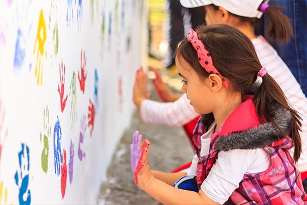 Zwei Mädchen die bunte Handabdrücke auf eine weiße Wand machen.