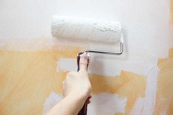 Eine Farbwalze mit der weiße Farbe auf eine orangene Wand gestrichen wird.