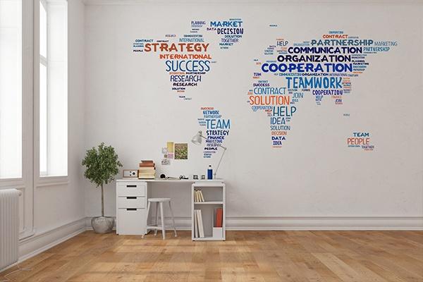 Eine weiße Wand mit einem großen Wandtattoo einer Weltkarte, die aus Worten besteht. Davor ein weißer Schreibtisch mit Hocker. Links daneben ein kleines Bäumchen in einem Topf.