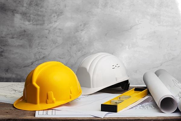 Ein gelber und ein weißer Bauarbeiterhelm liegen auf ein paar Bauplänen. Daneben liegt eine Wasserwaage und zwei weitere Rollen von Bauplänen.