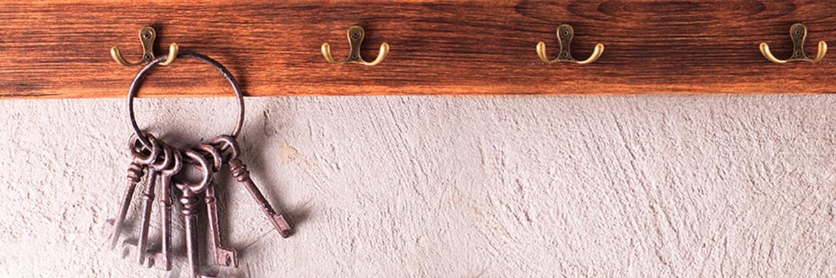 Ein Brett an einer Wand auf dem mehrere Haken geschraubt sind. Auf einem Haken ganz links hängt ein Schlüsselbund mit sechs alten Schlüsseln.