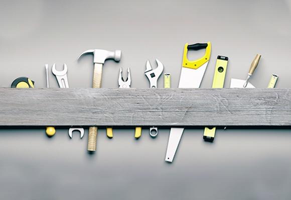 Ein Brett hinter dem ein Maßband, ein Schraubenzieher, ein Schraubenschlüssel, ein Hammer, eine Kombizange, ein weiterer Schraubenschlüssel, ein Zollstock, eine Säge, eine Wasserwaage, eine Kelle und ein weiter Zollstock stecken.