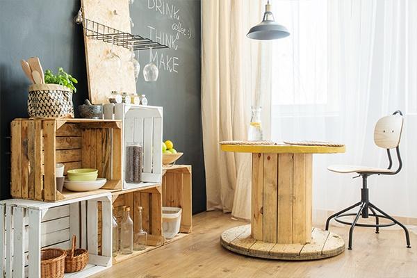 Upcycling von alten Holzkisten, die nun als Regal benutzt werden. Davor steht eine Kabeltrommel, die als Tisch benutzt wird. Dabei steht ein Drehstuhl.