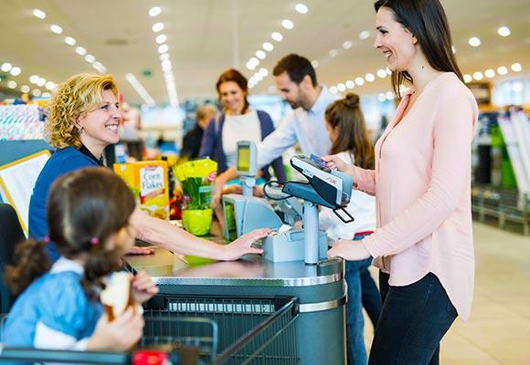 Eine Kundin kauft bei HOFER ein und bezahlt mit der Karte an der Kasse. Das Kind sitzt im Einkaufswagen und die Kassiererin lächelt.