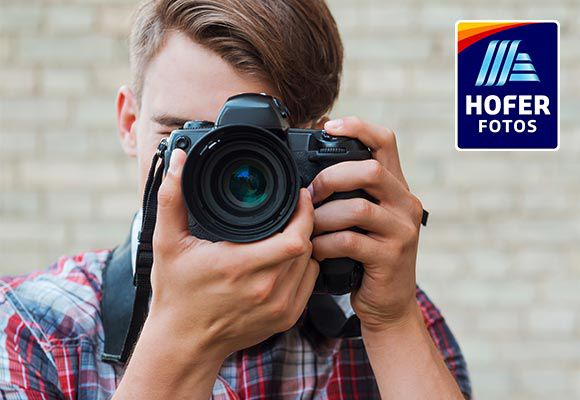 Ein junger Mann fotografiert den Betrachter. Rechts oben ist das Logo von HOFER FOTOS zu sehen.