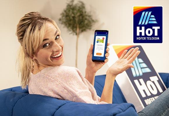 Eine Frau auf einer blauen Couch hält in der linken Hand ihr Mobiltelefon. Sie dreht sich zurück und lächelt in die Kamera. Dahinter ist das Logo von HoT zu sehen.