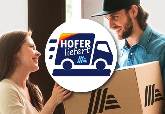 Ein Paketzusteller übergibt einer lächelnden Frau ein Paket von HOFER. Davor das HOFER liefert Logo.