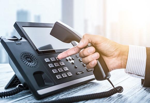 Eine Männerhand greift zum kabelgebundenen Telefonhörer und wählt eine Zahl des schwarzen Bürotelefons.