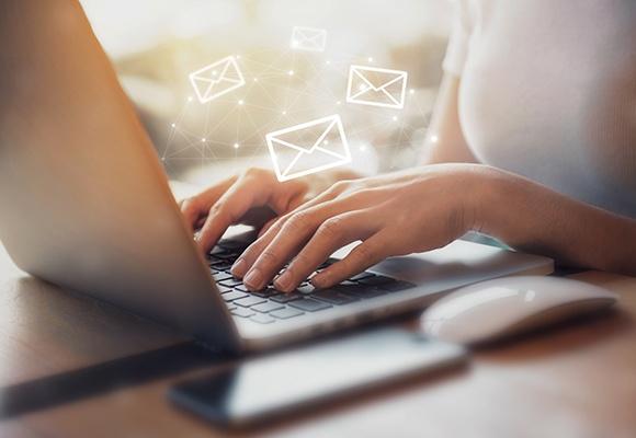 Frauenhände tippen auf einem silbernen Laptop. Briefsymbole schweben über ihren Fingern.
