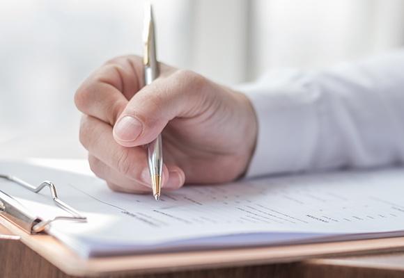 Eine Männerhand schreibt mit einem silbernen Kugelschreiber auf ein Blatt Papier, das auf einem Klemmbrett liegt.