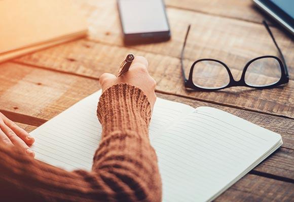 Eine Frau in braunem Pulli schreibt in ein liniertes Heft. Auf dem Holztisch vor ihr liegt eine schwarze Brille und ein Mobiltelefon.