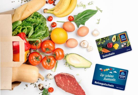 Ein Einkaufssackeler, Obst, Gemüse und je ein HOFER Warengutschein und ein HOFER Reisen Gutschein liegen auf einem weißen Hintergrund..