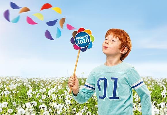 Ein junge mit roten Haaren und einem blauen Langarmshirt steht auf einer Wiese und pustet in eine Windrad mit dem Logo für Projekt 2020.