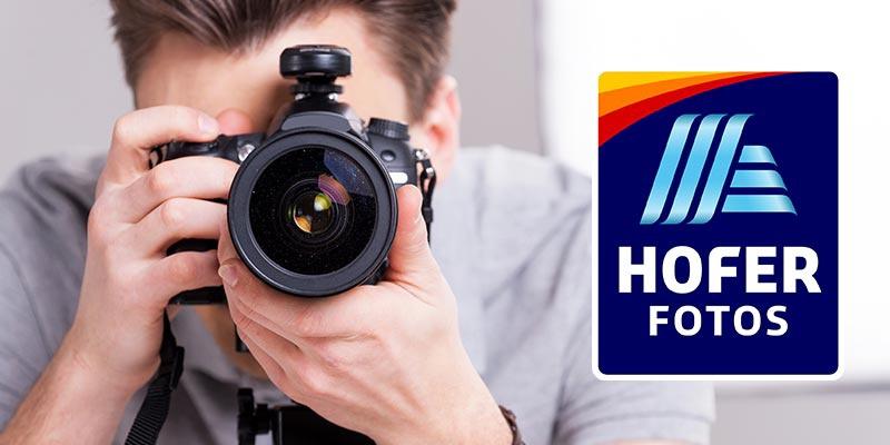 Ein Mann sieht durch seine Kamera und fotografiert den Betrachter. Daneben das Logo von HOFER FOTOS.