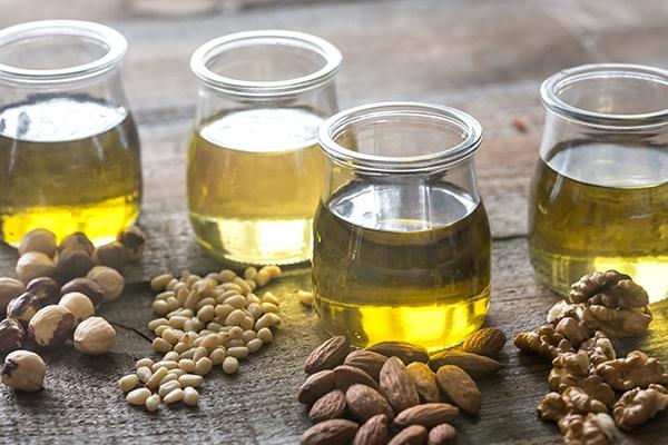 Vier Gläser mit unterschiedlichen pflanzlichen Ölen stehen auf einer Holzfläche. Davor sind unterschiedliche Nusssorten gestreut.