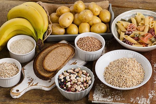 Bananen, eine kleine Schachtel mit Kartoffeln, mehrere Schüsseln mit unterschiedlichen Getreidearten und eine Schüssel mit Pasta sind auf einem Holztisch zu sehen.