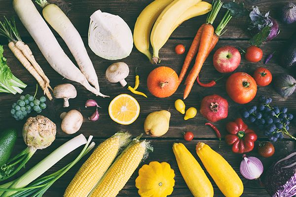 Unterschiedliche Obst- und Gemüsesorten liegen auf einem dunklen Holzuntergrund.