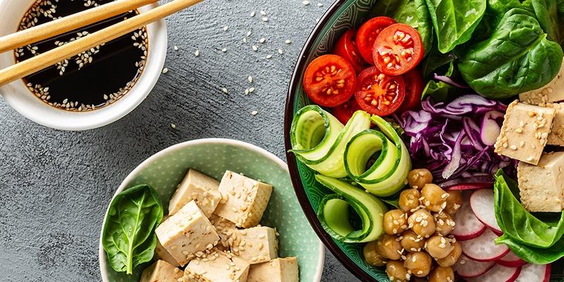 Eine grüne Schüssel mit Salat, Gurken, Tomaten, Kichererbsen, Radieschen und Tofuwürfel.