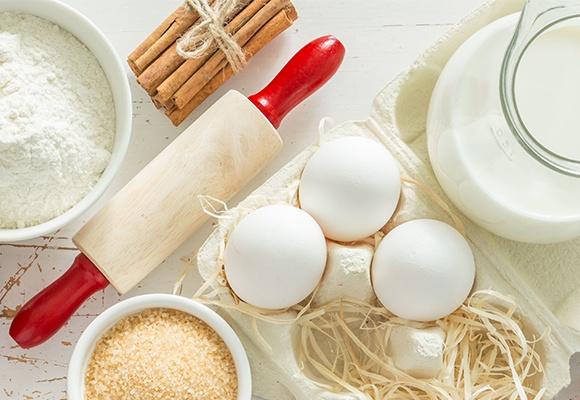 Eine Schüssel Mehl, eine mit braunem Zucker und drei weiße Eier. Daneben eine Kanne Milch und ein Bund Zimtstangen.