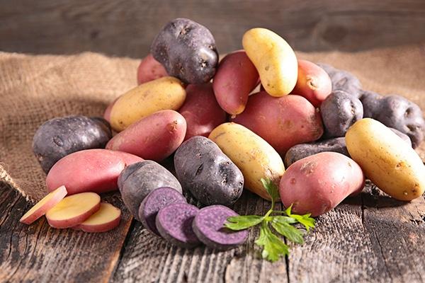 Unterschiedliche Kartoffelsorten liegen auf einem Holzuntergrund. Dahinter ein Jutesack.