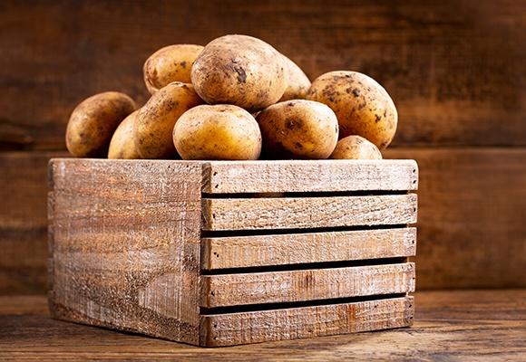 Eine Holzkiste mit Kartoffeln.
