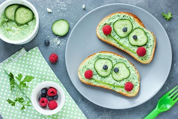 Zwei Brote mit Gurkenaufstrich liegen auf einem grauen Teller. Die Gurken, Schnittlauch und Beeren formen ein Gesicht auf dem Brot.