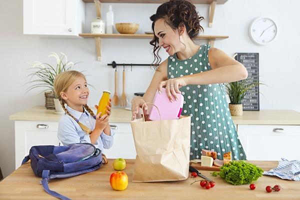 Eine Mutter und ihre Tochter stehen in der Küche und packen eine gesunde Jause in eine Papiertasche.