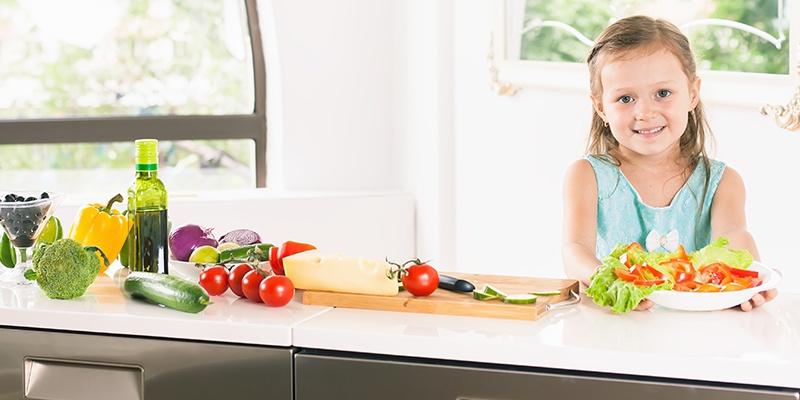 Ein lächelndes Mädchen stellt einen Teller mit geschnittenem Salat und Paprika auf einen Tisch.