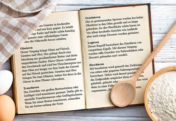 Ein aufgeschlagenes Kochbuch, indem verschiedene Zubereitungsmethoden erklärt werden.