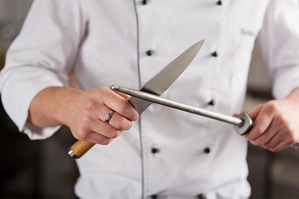 Ein Koch beim Messer schärfen.
