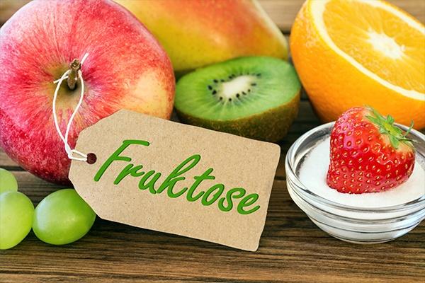 Ein Apfel, eine Kiwi, eine Orange und eine Erdbeere in einer Schüssel mit Zucker sind auf einer Holzfläche. Im Vordergrund ist auf einem Papier der Schriftzug