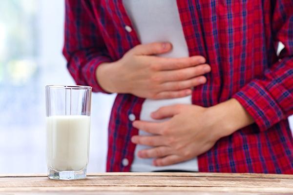 Ein Glas Milch steht im Vordergrund. Im Hintergrund sieht man einen Mann, der beide Hände auf den Bauch legt, als würde er schmerzen.