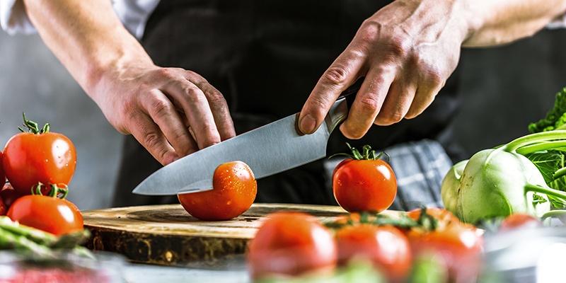 Ein Mann mit schwarzer Schürze schneidet eine Tomate auf einem Holzschneidebrett.