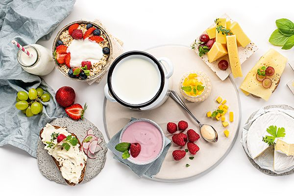 Joghurt und Topfen in Schüsseln von oben betrachtet. Daneben ist ein bestrichenes Brot, eine Müslischale, aufgeschnittener Hart- und Weichkäse.