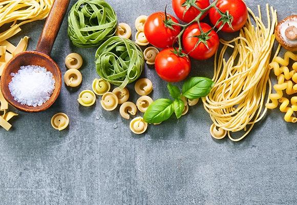 Unterschiedliche Sorten von Pasta liegen auf grauem Untergrund.