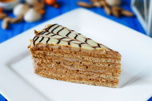 Ein Stück Esterhazy Torte auf einem weißen Dessertteller.