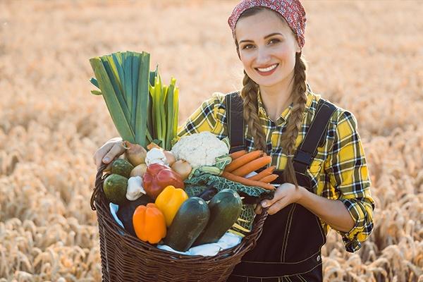 Eine Jungbäuerin mit zwei Zöpfen, die auf einem Getreidefeld steht. Sie hält einen Korb mit frischem Gemüse hoch.
